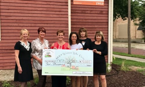 100 Women Who Care standing with a large check
