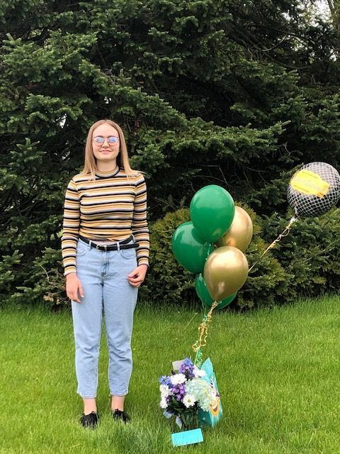 Girl standing in yard with balloons